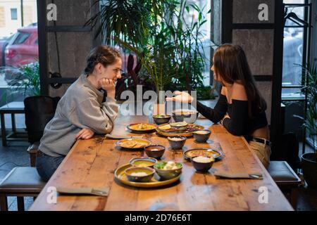 Zwei Freundinnen sitzen und essen in einem Café.