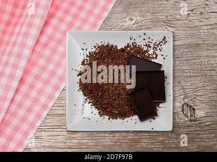 Geriebene Schokolade auf einem weißen Teller. Teller steht auf altem Holz und karierter Tischdecke. Dunkle Schokolade von oben fotografiert. - Stockfoto