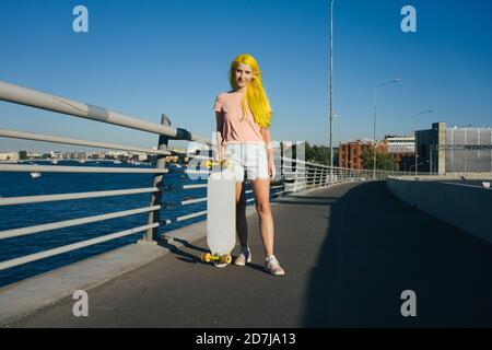 Junge Frau, die an sonnigen Tagen mit Skateboard auf der Brücke steht - Stockfoto