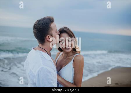 Mann, der Frau küsst, während er am Strand steht