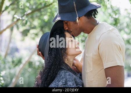 Mann küsst Frau auf der Stirn, während im Park stehen