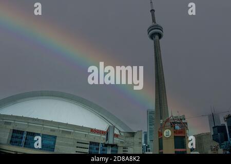 Downtown Toronto City, Kanada, Juli 2015 - CN Turm und Kuppel von Rogers Zentrum mit Regenbogen im Hintergrund an einem düsteren Tag