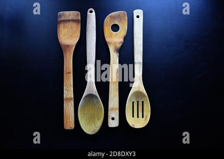 Alte Holzküche, Holzlöffel, Holzgabel, Spachtel und mehr auf schwarzem Hintergrund