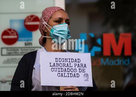"""Madrid, Spanien. Oktober 2020. Eine Krankenschwester protestiert mit einem Plakat mit der Aufschrift """"Arbeitswürde für eine qualitativ hochwertige Versorgung"""", während das Gesundheitspersonal im La Princesa Krankenhaus eine Demonstration gegen die mögliche Verlegung des Gesundheitspersonals in das neue Isabel Zendal Notkrankenhaus abhält, die die Regionalpräsidentin von Madrid Isabel Diaz Ayuso angekündigt hat. Isabel Zendal Emergency Hospital wird in den kommenden Tagen eingeweiht und wird eine Kapazität von 1,000 Betten für Coronavirus (COVID-19) Fälle haben. Quelle: Marcos del Mazo/Alamy Live News"""