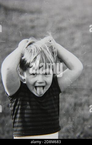 Feine 70er Jahre Vintage Schwarz-Weiß-Fotografie von einem jungen Mädchen genießen ihren Sommer Spaß im Hinterhof.