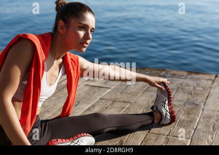 Außenaufnahme der attraktiven Fitness-Frau, die sich vor dem Joggen aufwärmt, auf dem Pier sitzt und die Beine dehnt Stockfoto