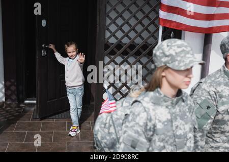 Lächelnde Tochter mit winkender Hand, die in der Tür in der Nähe von american steht Flagge mit verschwommener Mutter und Vater in Militäruniformen auf Vordergrund - Stockfoto