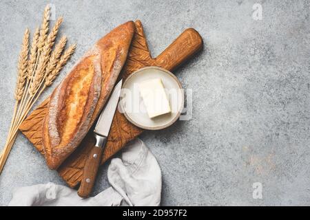 Frisches Baguettebrot und Butter auf Betongrund. Kopieplatz für Text in der Draufsicht