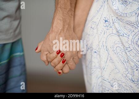 Ausgeschnittene Aufnahme eines älteren Paares, das die Hände hält