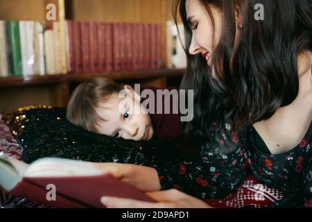 Eine junge Frau liest einem Kind ein Buch vor. Eine Mutter lehrt ihren kleinen Jungen zu lesen.