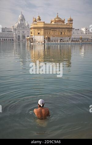 Amritsar, Punjab, Indien, August 2012. Ein Sikh-Mann nimmt ein zeremonielles Bad im Goldenen Tempel. Auch bekannt als Sri Harmandir Sahib ('Aufenthaltsort Gottes') ist t