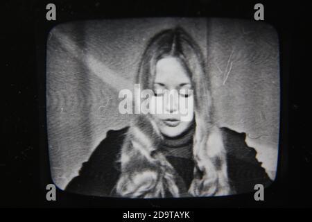 Schöne Vintage-Schwarz-Weiß-Fotografie einer jungen Frau aus den 1970er Jahren, die im fernsehen sendet. - Stockfoto