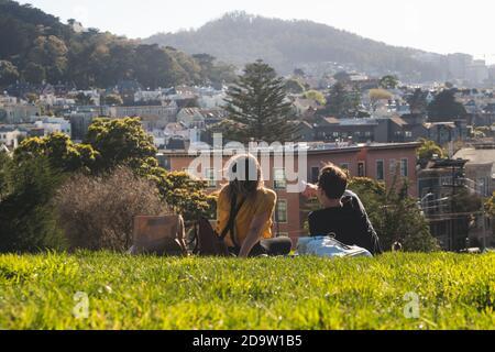San Francisco, Kalifornien, USA - MÄRZ 15 2019: Leute, die ein Picknick im Alamo Square Park an einem sonnigen Tag mit blauem Himmel machen