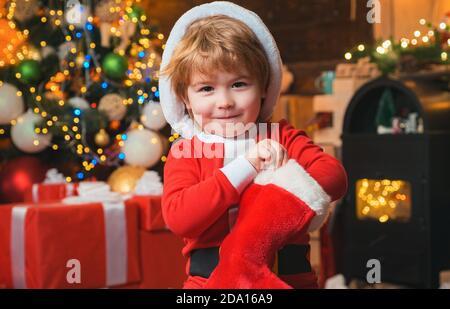 Oh, glücklicher Tag. Kind fröhliches Gesicht bekam Geschenk in weihnachtsstrumpf. Inhalt der weihnachtsstrumpf. Freude und Glück. Kindheitsmomente. Kind Junge santa Hold