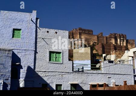 Blick auf Mehrangarh (Mehran Fort) von der alten Blauen Stadt. Ziegelmauer des alten Hauses auf einem Vordergrund. Jodhpur, Rajasthan, Indien