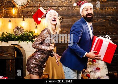 Weihnachten Herrenanzug Mode. Verliebte Paare. Betrunkene Mädchen feiern Neujahr. Weihnachtliche Innenausstattung. Nette junge Frau und schöner Mann mit Santa - Stockfoto