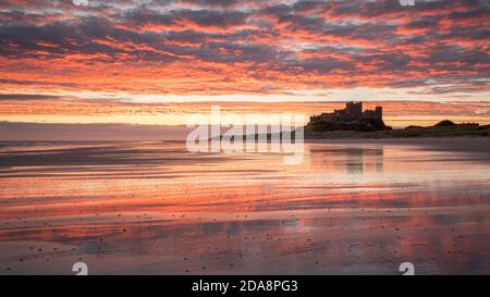Ein lebhafter Sonnenaufgang spiegelt sich im nassen Sand am Bamburgh Beach wider, mit der silhouettierten Burg, die auf einem Felsvorsprung am Horizont thront.