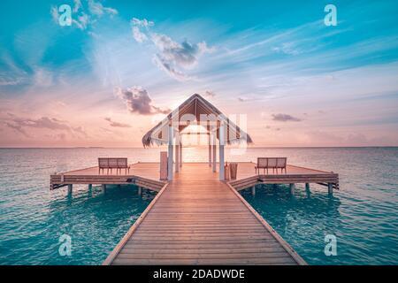 Sonnenuntergang auf der Insel der Malediven, Luxus-Wasservillen-Resort und hölzerner Pier. Schöner Himmel und Wolken und Strand. Toller Sommerurlaub, Aussicht zum Entspannen
