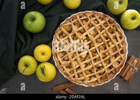 Apfelkuchen auf grünem Stoff Hintergrund. Frische gelbe Äpfel, Zimtstangen auf einem Tisch. Dessertideen für den Herbst.