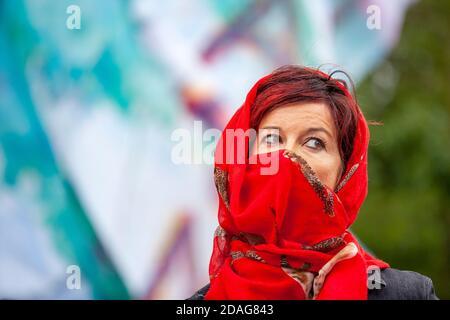Eine attraktive Frau mittleren Alters trägt einen roten Kopfschal über Kopf und Gesicht während eines Extinction Rebellion Protestes vor Shell UK Hauptquartier.