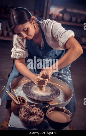 Stilvoller professioneller Töpfer-Bildhauer arbeitet mit Ton auf einem Potter-Rad und am Tisch mit den Werkzeugen. Handarbeit.