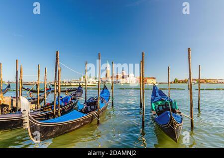 Gondeln, die in Venedig an Wasser angedockt sind. Gondoliere segeln San Marco Wasserlauf. Insel San Giorgio Maggiore mit Campanile San Giorgio in Vene