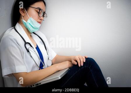 Asiatische junge Frau Arzt tragen Maske zur Sicherheit Coronavirus sitzen auf der Ecke Boden schlafen mit Erschöpfung von Überarbeit Konzept kümmern sich ist