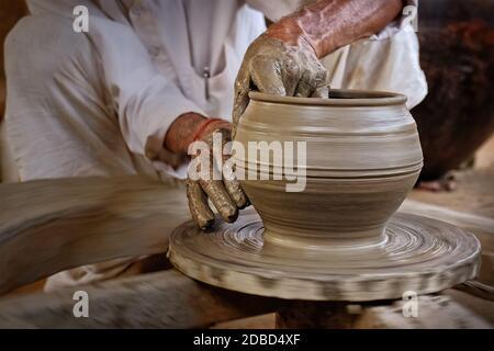 Indischer Töpfer bei der Arbeit: Das Töpferrad werfen und Keramikgefäß und Tonwaren Formen: Topf, Glas in Töpferwerkstatt. Erfahrener Meister. Handwor