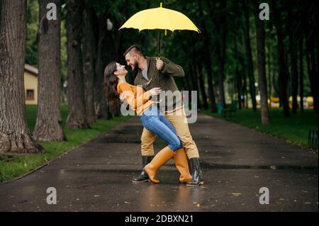 Glückliche Liebe Paar tanzen im Park im Sommer regnerischen Tag. Mann und Frau Umarmungen unter Regenschirm im Regen, romantische Datum auf dem Wanderweg, nasses Wetter in Gasse Stockfoto
