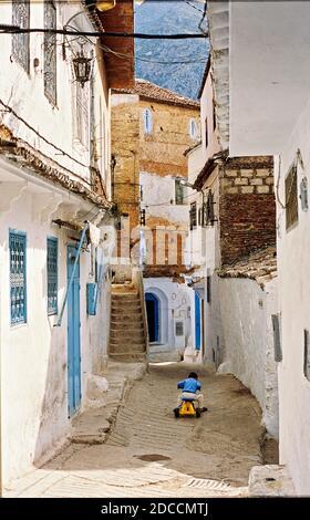 Straßen und Gassen der Medina von Chefchaouen, Marokko. Ein Kind spielt auf der Straße