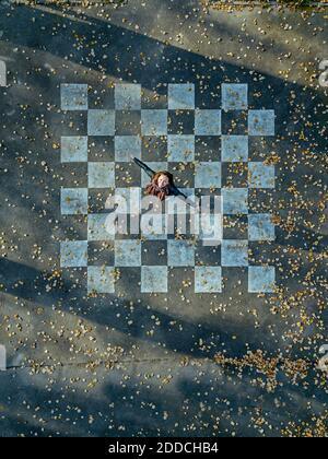 Mittlere Erwachsene Frau mit ausgestreckten Armen Spinnen auf Asphalt gemalt Mit Schachbrettmuster