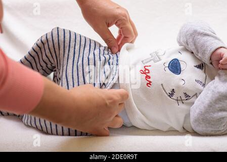 Mutter ändert eine Windel auf neugeborenem Baby