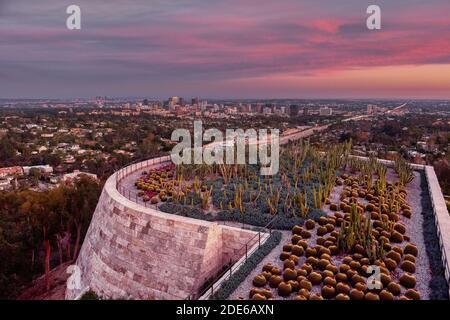 Blick vom Getty Center Cactus Garden auf die Skyline von Los Angeles bei Sonnenuntergang mit verschiedenen Kakteen im Vordergrund, Los Angeles, USA - Stockfoto