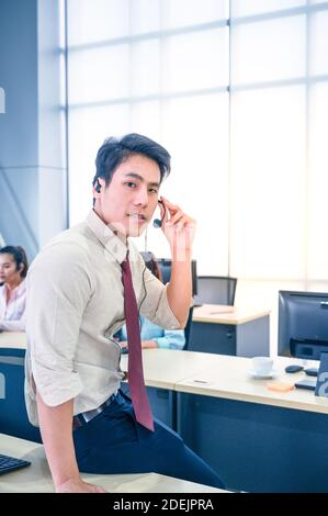 Junge Kundendienstmitarbeiter mit Headsets und Computer arbeiten im Büro. Professionelles Bedienkonzept. Stockfoto