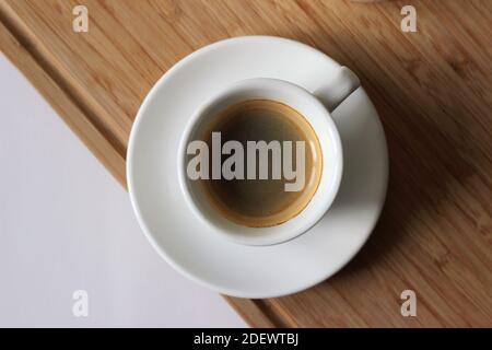 Tasse frischer starker Espresso auf Holzbrett serviert. Kaffee Wird Aufgewärmt. - Stockfoto