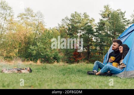Schönes Paar sitzt am Eingang des Zeltes mit Tassen in den Händen und Blick auf das Lagerfeuer