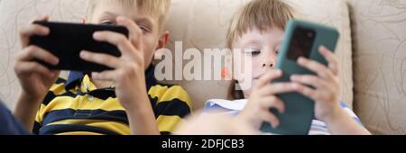 Kinder halten das mobile Gerät in den Händen und spielen. - Stockfoto