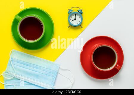 Teetrinken. Im Café befinden sich zwei blaue medizinische Schutzmasken auf dem Tisch. Zwei Tassen aus Keramik mit roten Untertassen und Kaffee auf einem gelben und weißen Stockfoto