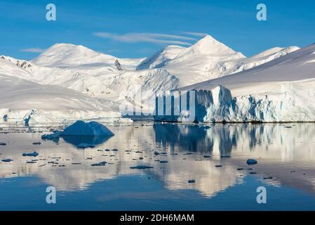 Schneebedeckte Insel und Eisberg mit Reflexion im Südatlantik, Antarktis