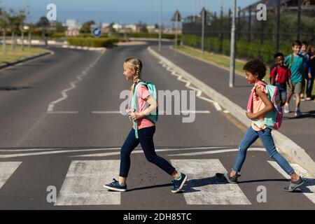 Zwei Schulmädchen, die auf einem Fußgängerübergang die Straße überqueren