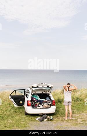 Rückansicht der Frau, die sich mit dem Auto auf dem Feld gegen die Strecke streckt Meer - Stockfoto