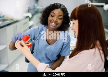 Nahaufnahme horizontale Aufnahme von ziemlich jungen lächelnden afrikanischen Frau Zahnarzt, erklärt Möglichkeiten der Behandlung oder Zähne Anatomie für ihre weibliche Patientin, zeigt