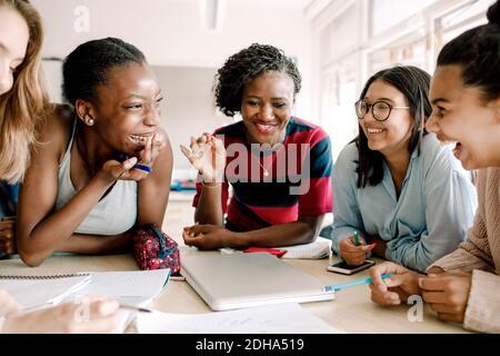 Lächelnder Lehrer gestikulierte, während fröhliche Schüler am Tisch sitzen Schulungsraum