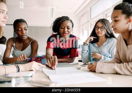 Lehrerin erklärt, während Schülerinnen am Tisch im Klassenzimmer studieren