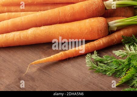 Frische Bio-Roh-Karotten auf einem dunklen rustikalen Holzhintergrund