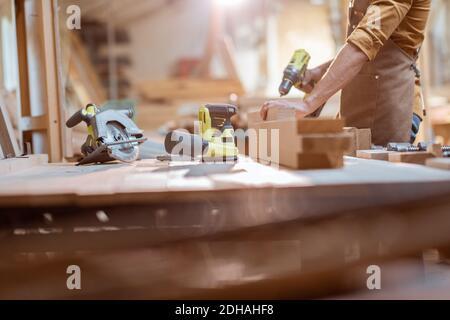 Zimmermann arbeitet mit modernen Akku-Werkzeugen und Holzstangen auf Die Werkbank in der Werkstatt