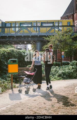 Vater trägt Tochter auf den Schultern, während Mutter schieben Baby Kinderwagen Am Fußweg gegen die Eisenbahnbrücke Stockfoto