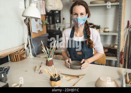 Kaukasische Frau, die keramische Suppenteller macht, während sie schützendes Gesicht trägt Maske für Coronavirus Prävention - Weibliche Person bei der Arbeit im Inneren Ihr kreatives po
