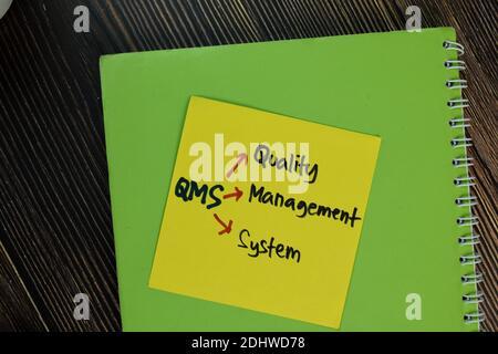 QMS - Qualitätsmanagementsystem Schreiben Sie auf Haftnotizen isoliert auf Holztisch.