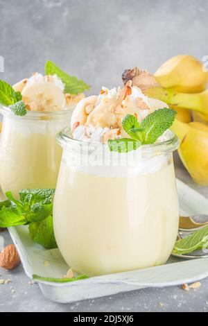 Frischer Bananenpudding zum Frühstück, Bananenjoghurt. Süßes Dessert in Gläsern mit Bananenscheiben und Nüssen, roher vegetarischer Snack, auf grauem Beton backgr